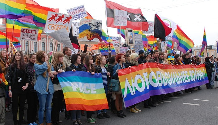 A group of people holding banners and flags walking on the road